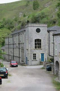A stone building with several cars parked outside.