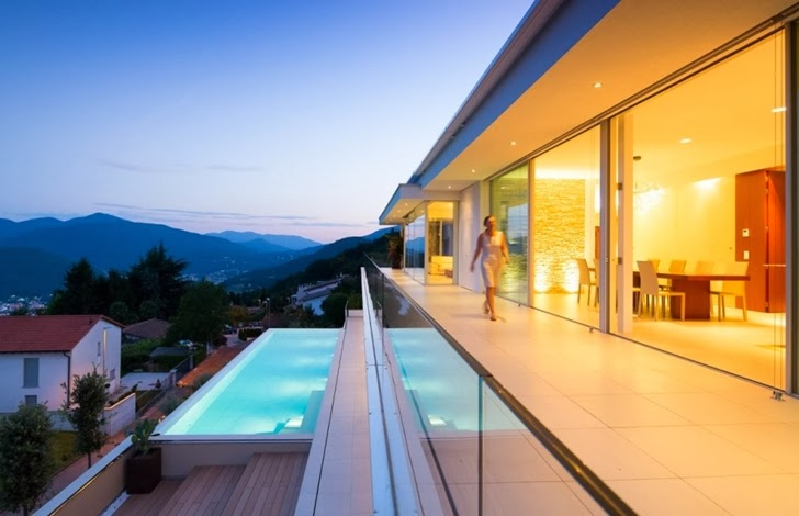 Terrace and swimming pool in Beautiful House Lombardo by Philipp Architekten at dusk
