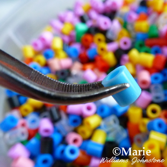 Picking up fused Perler beads with a pair of curved tweezers