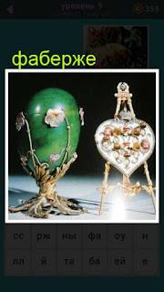 на столе стоят два произведения Фаберже, яйца с драгоценностями