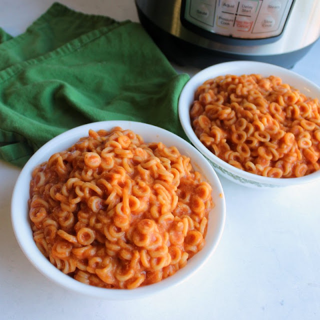 close up of two bowls full of saucy homemade spaghettios in front of instant pot
