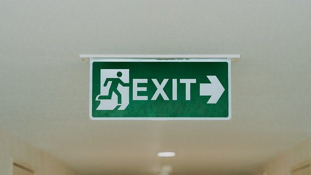 A green and white exit sign, with arrow pointing right