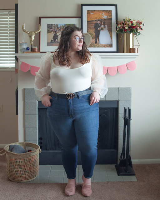 An outfit consisting of a cream bodice and white organza puffy princess sleeves crop top tucked into blue high waist denim jeans and dusty pink pointed toe mules.