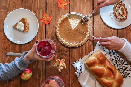photograph of people celebrating Thanksgiving with pumpkin pie and challah