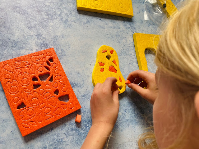 Overhead shot showing a child assembling the 3D foam puzzle giraffe