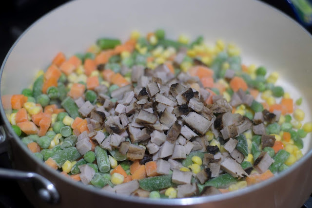The diced pork chop and vegetables in the pan.