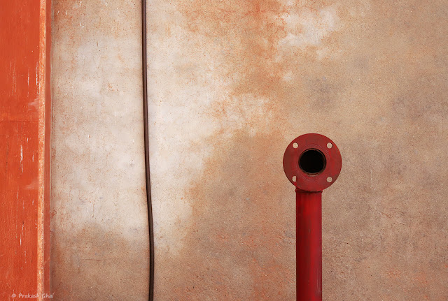A Minimalist Photograph of a Red Industrial Pipe versus the Black wire on a textured wall near Jaleb Chowk Old Jaipur City.