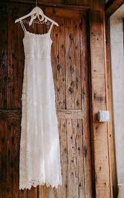 Vestido de novia colgado de una percha sobre un fondo de madera