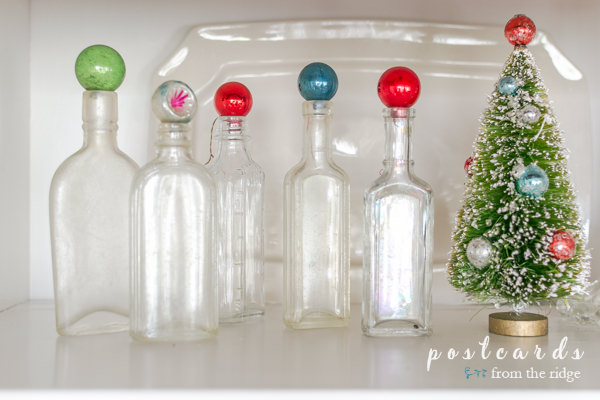 little glass ornaments on top of vintage glass bottles