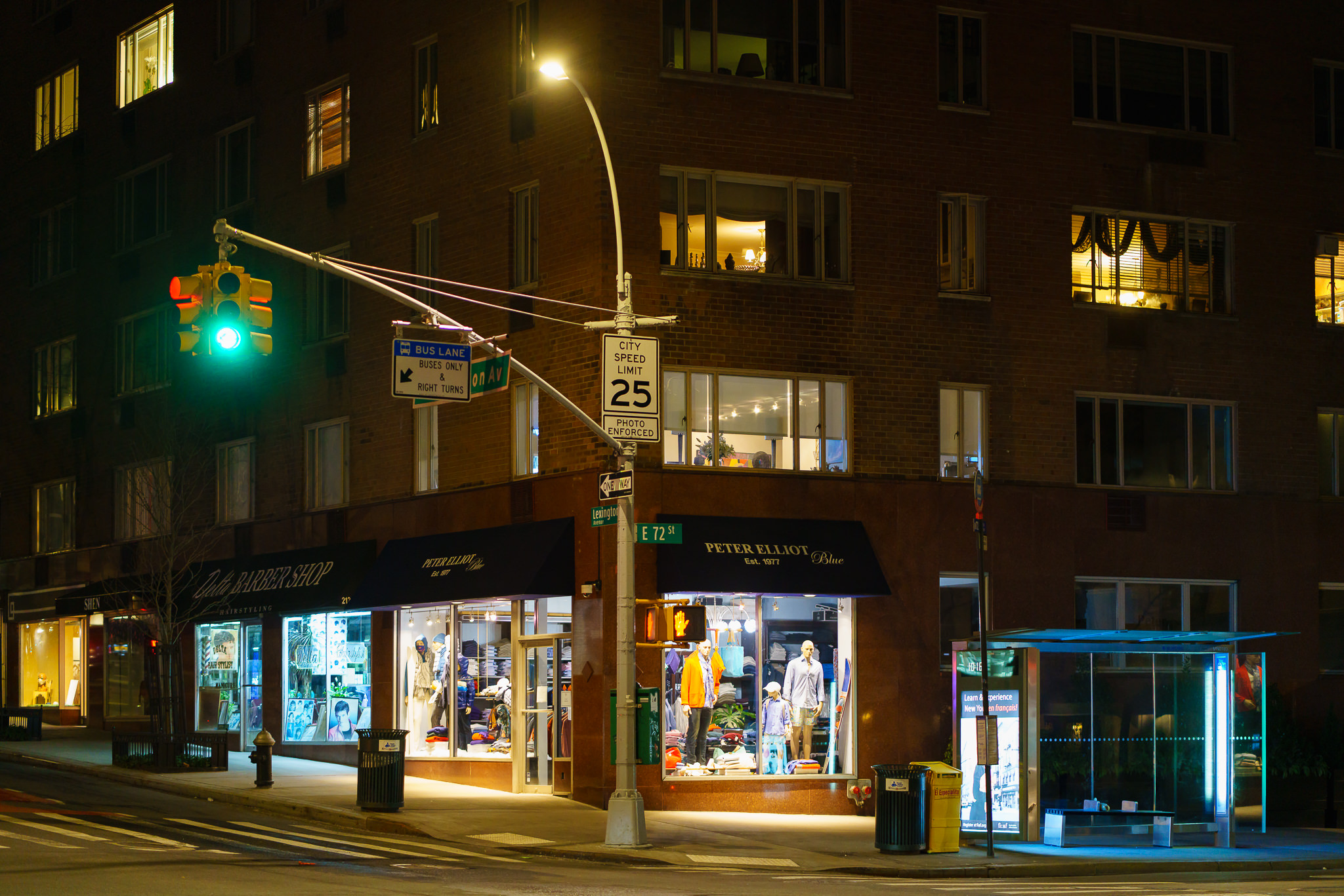 a photo of shops at a new york city intersection at night