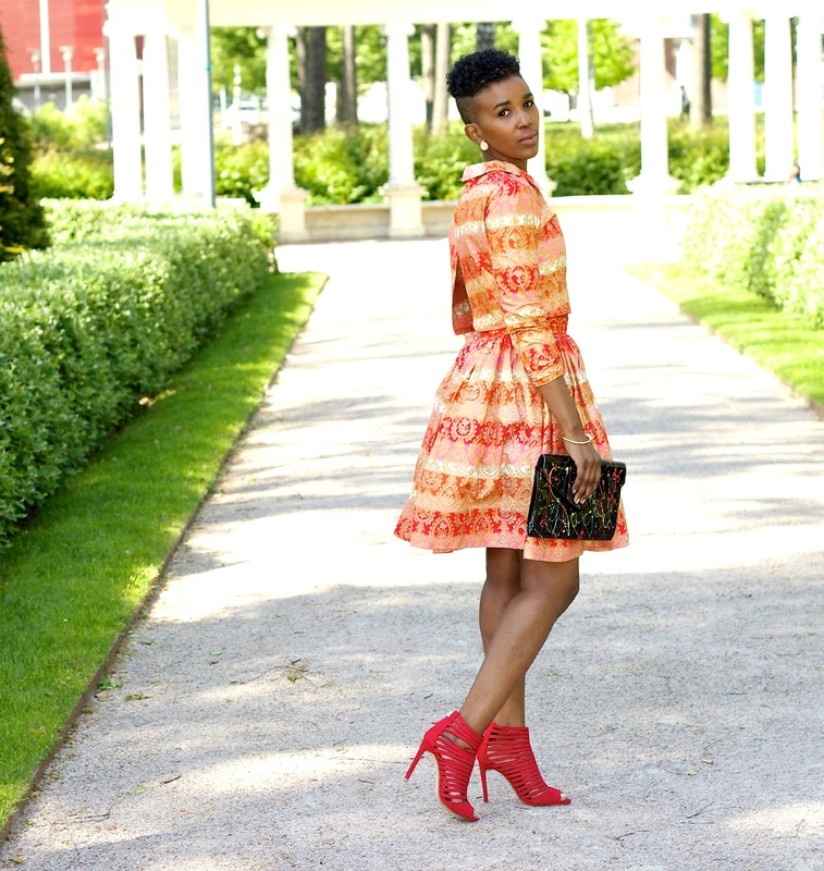 side pose of woman wearing african print outfit with a pair of red heels
