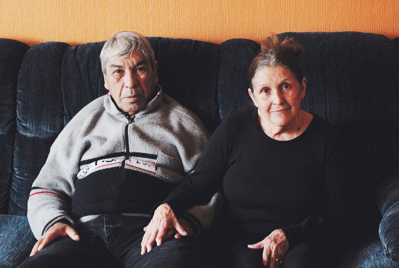 Older couple sitting on the couch sharing their live stories