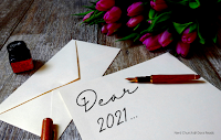 'Dear 2021...' written in fancy writing on a piece of paper, on top of a desk which for some reason also has a bunch of tulips on it