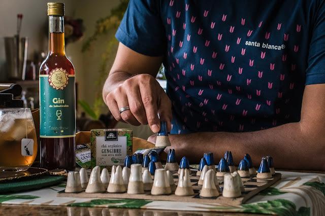 homem jogando xadrez enquanto toma um drink com gin