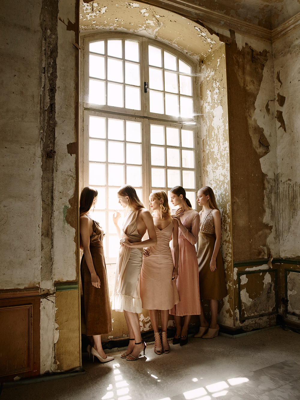 Models in pastels at window of decaying French Chateau Gudanes