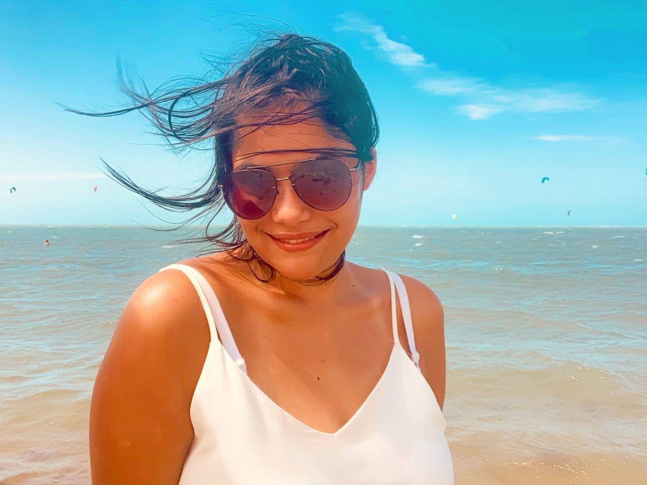 mulher de blusa branca e óculos escuro em frente a praia