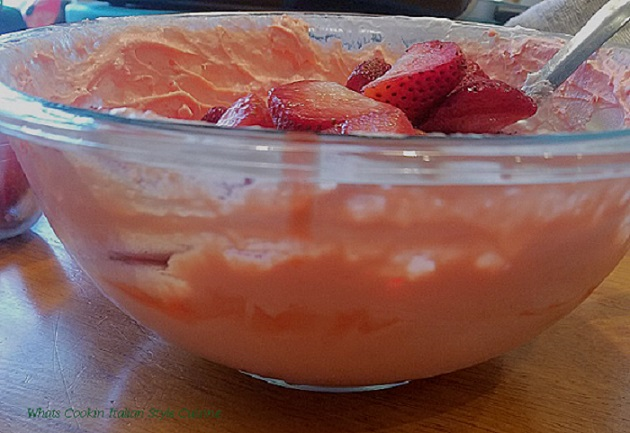 whipped cream in a bowl with strawberries, strawberry jello mixed with vanilla pudding to make a filling for a pie