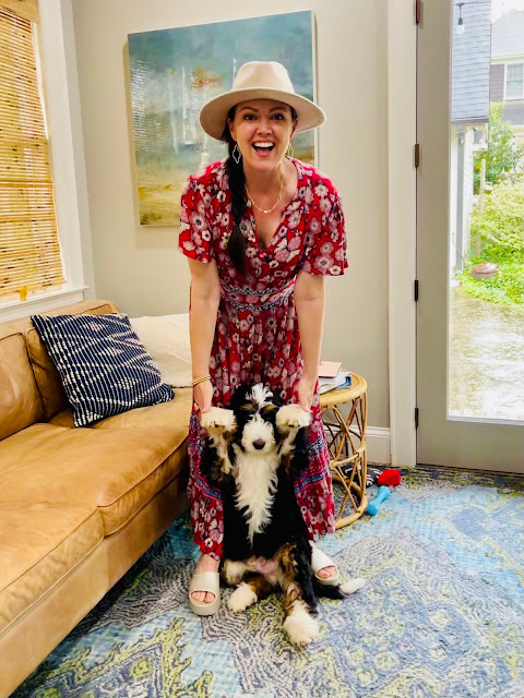 woman in a red dress and tan hat holding a big puppy