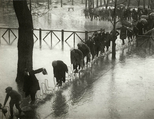 40 Amazing Historical Pictures - People walking on the chairs at the Maisons-Laffitte racecourse to escape the river Seine flood. Paris. 1924.