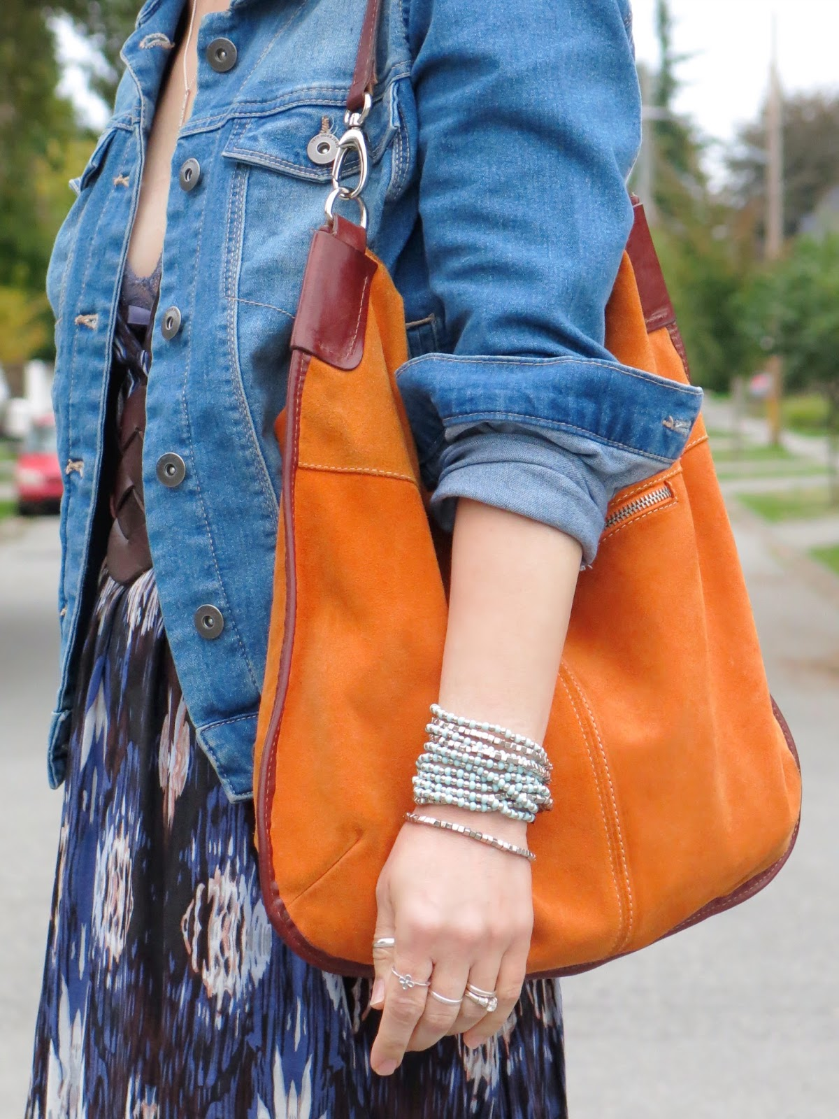 printed maxi-dress, denim jacket, and orange suede bag