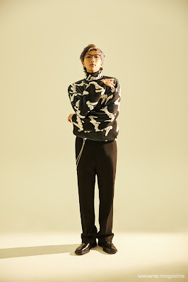 RM w okularach stojący prosto, z prawą dłonią skierowaną w lewo