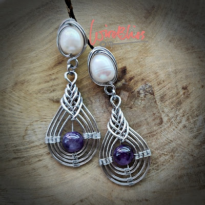 Wire wrapped Pipa earrings with pearl and amethyst lying on wood surface