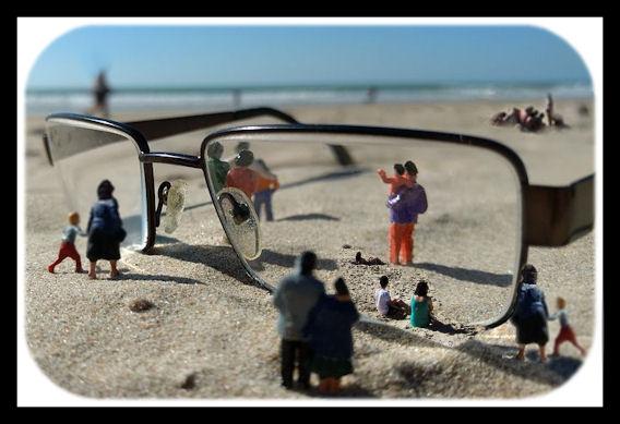 Uimarantanäkymä, jossa hiekalla epäselviä hahmoja ja korostetun suuret silmälasit, joitten linssissä tarkemmin ihmisiä.