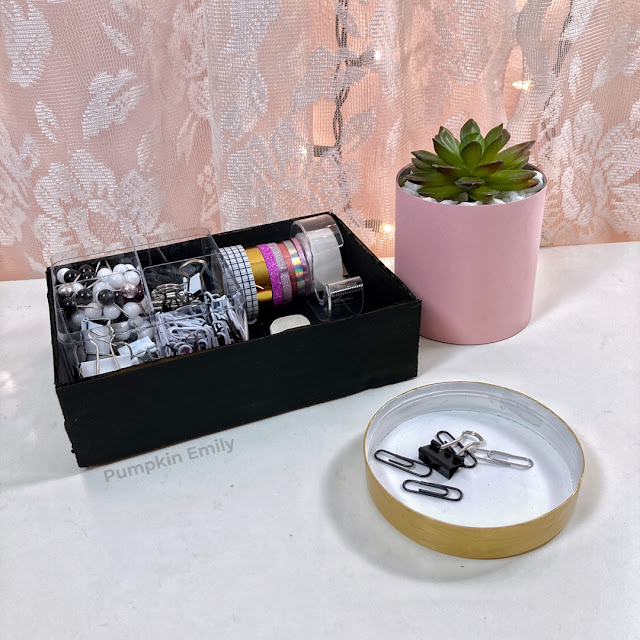 A cardboard tray, tin can planter, and a dish made from a plastic lid.
