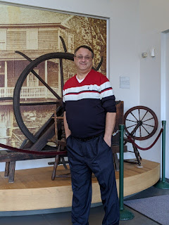 Man wearing blue pants and a blue shirt with red and white stripes. He is standing in front of a museum exhibit that includes a large black and white photo of a house, a spinning wheel, and a larger wheel on a frame