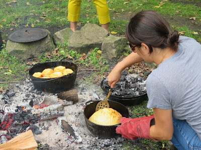 Cast iron cooking pots over outdoor fire with bread and biscuits in them, a woman tends to one of the pots