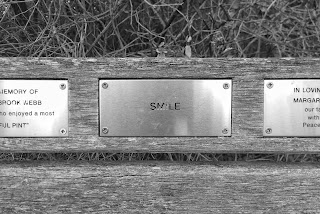 """Close-up of a metal plaque on a bench that reads """"Smile"""""""