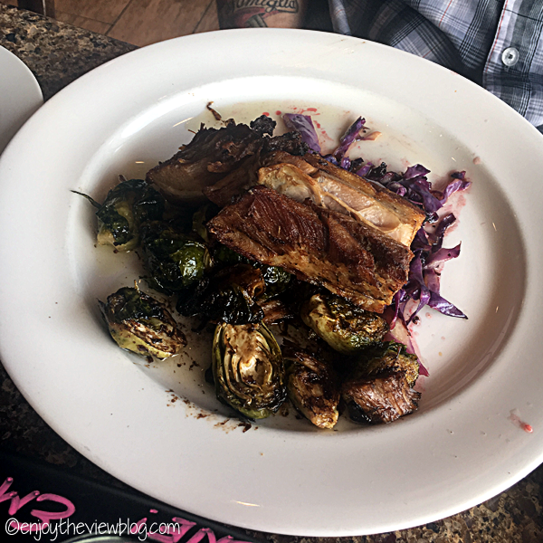 pork belly with brussel sprouts and braised red cabbage on a white plate