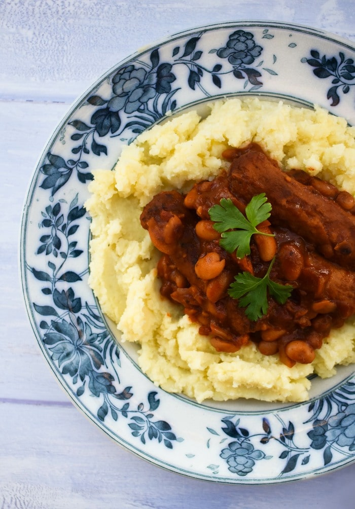 a close up of sausage stew serve in a blue patterned bowl with mashed potato