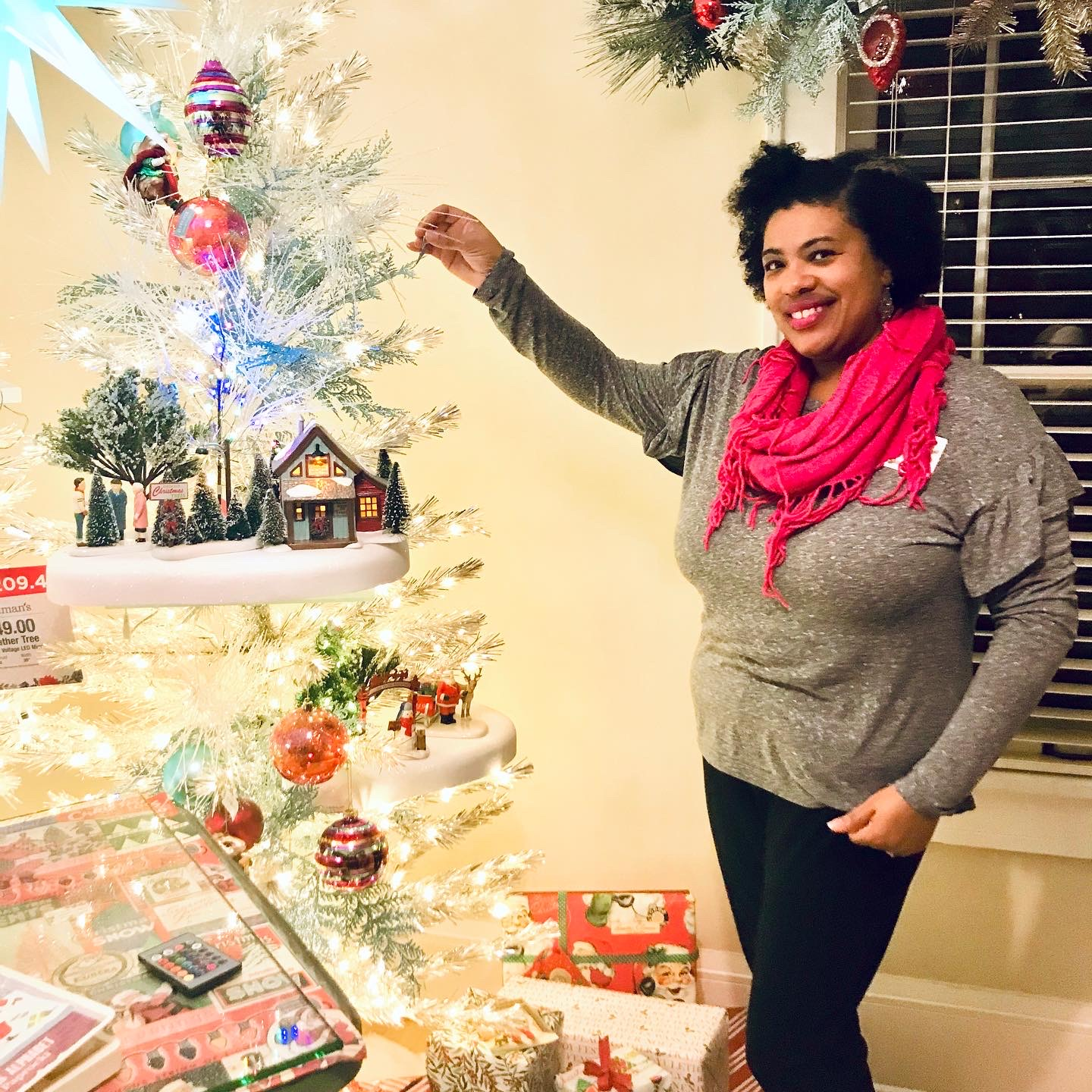 a black woman standing next to a whimsical white Christmas tree