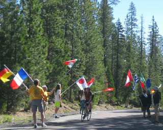 Cyclist pedals through volunteers waving international flags at the Gumboot water stop, W A Barr Road, Mt. Shasta, California