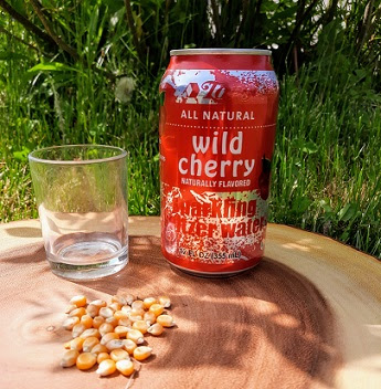 The materials needed to conduct the Dancing Popcorn experiment are sitting on a tree stump: seltzer water, popcorn kernels, and a clear glass.