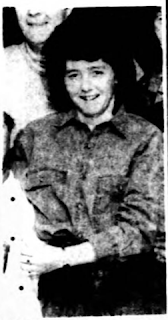 Black and white photo of a smiling woman in relaxed pose and casual clothes