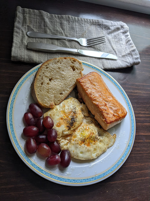 A table with window light falling on a grey napkin and cutlery, plate of salmon, eggs, Sourdough toast, and grapes