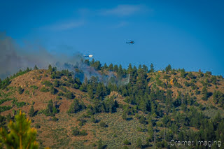 Cramer Imaging's landscape photograph of a helicopter dropping water on a wildfire near Panguitch Lake Utah