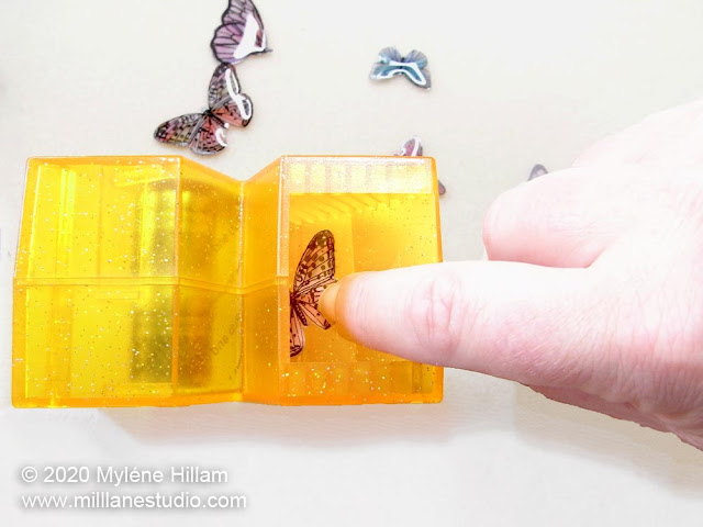 Placing the resin-coated butterfly into the well of the sticker making machine