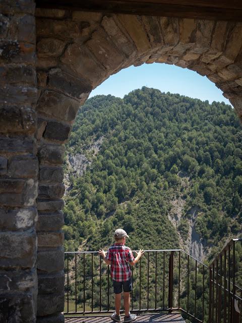 Niño bajo un arco del castillo de Boltaña asomado a las montañas