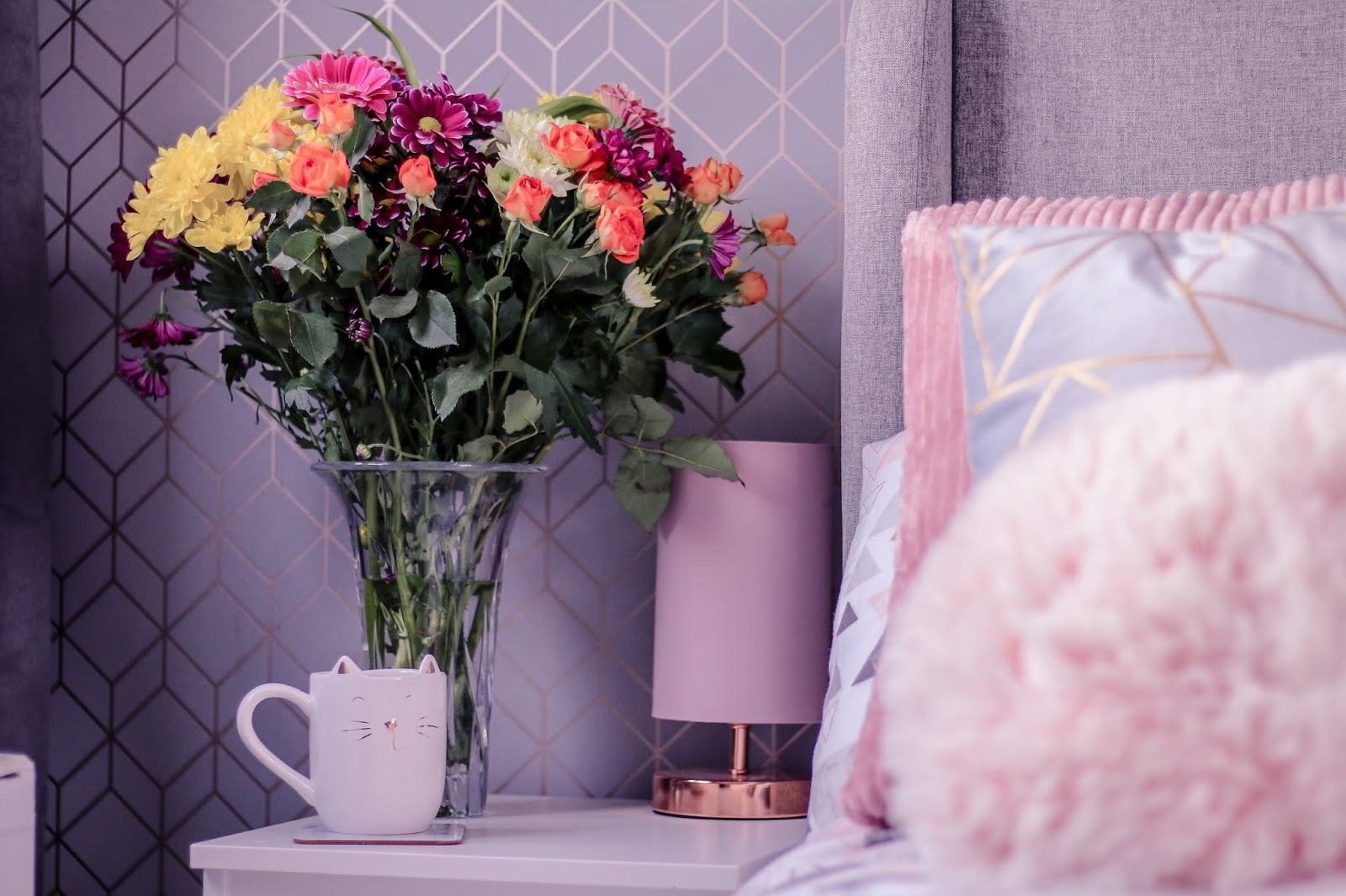 Landscape photo of a cat mug on a white bedside drawer with a bunch of pink and yellow flowers in a vase