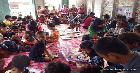 Anak-Anak di dampingi orang tua nya serius membaca