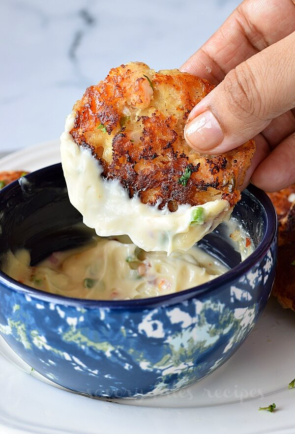 hand holding shrimp cake dipped in aioli
