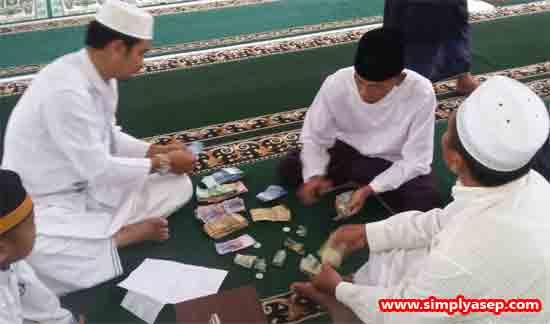 KOTAK AMAL : Proses penghitungan kotak amal Sholat Jumat perdana di Masjid Babussalam Duta Bandara Kubu Raya. Terdapat beberapa lembar mata uang Ringgit Malaysia dalam penghitungan ini.  Foto Asep Haryono