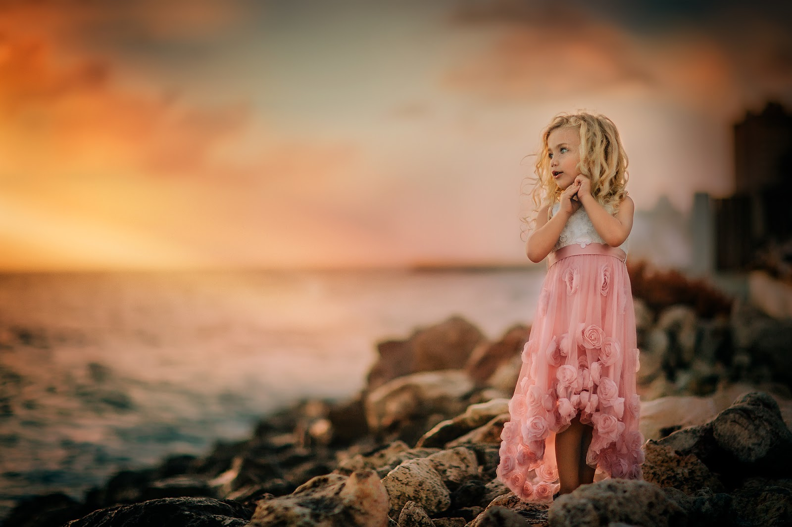Canon 5D mark III golden hour fine art portrait of a mesmerized little girl in a pink dress watching a beautiful sunset at Pietermaai Beach Curacao by Willie Kers