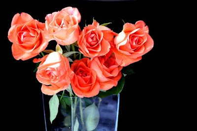 Roses oranges dans un vase transparent.