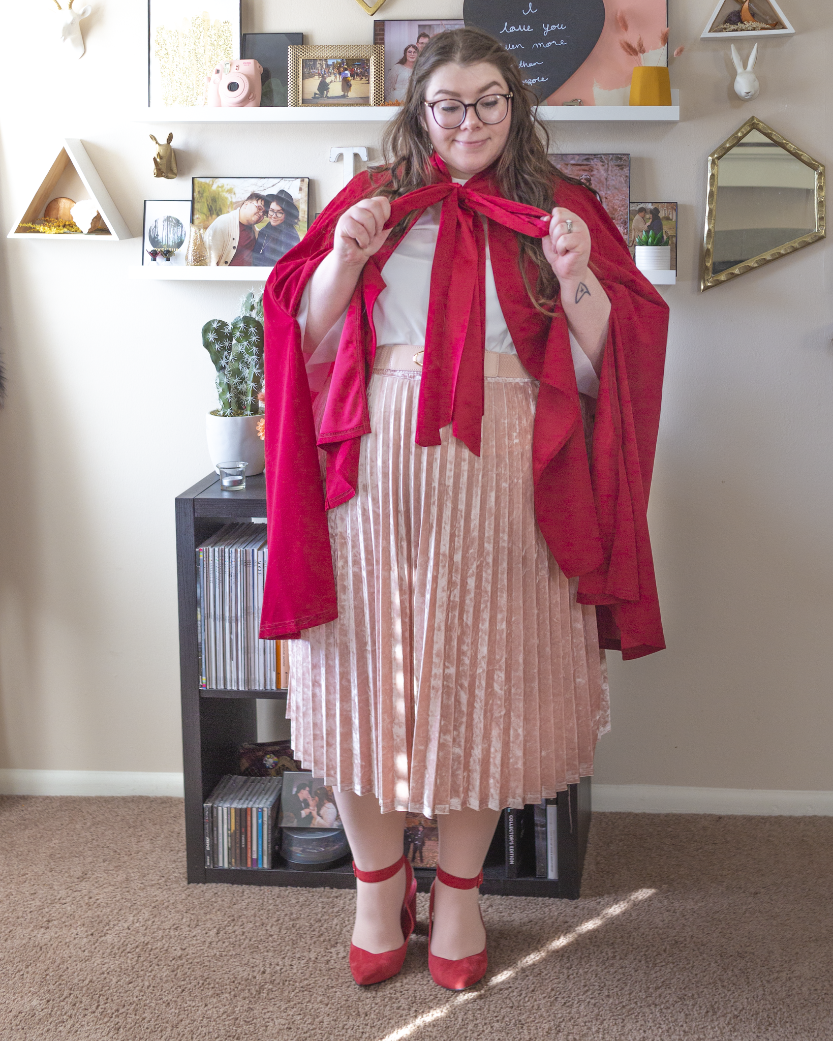 An outfit consisting of a red cape tied into a bow around the neck over a white high neck blouse, tucked into a pastel pink velvet pleated midi skirt and red ankle strap heels.