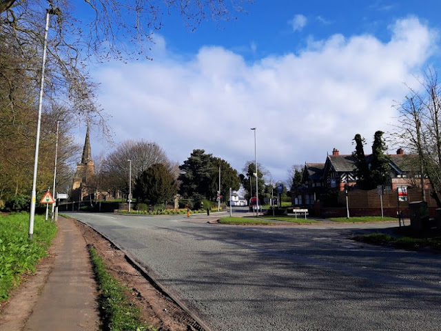 Image shows St Oswald's Church, Winwick, to the left and The Swan pub to the right.  The road in the centre of the picture is empty of traffic