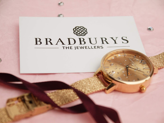 a rose gold olivia burton watch lay on pink tissue paper with a white bradburys the jewellers business card behind it